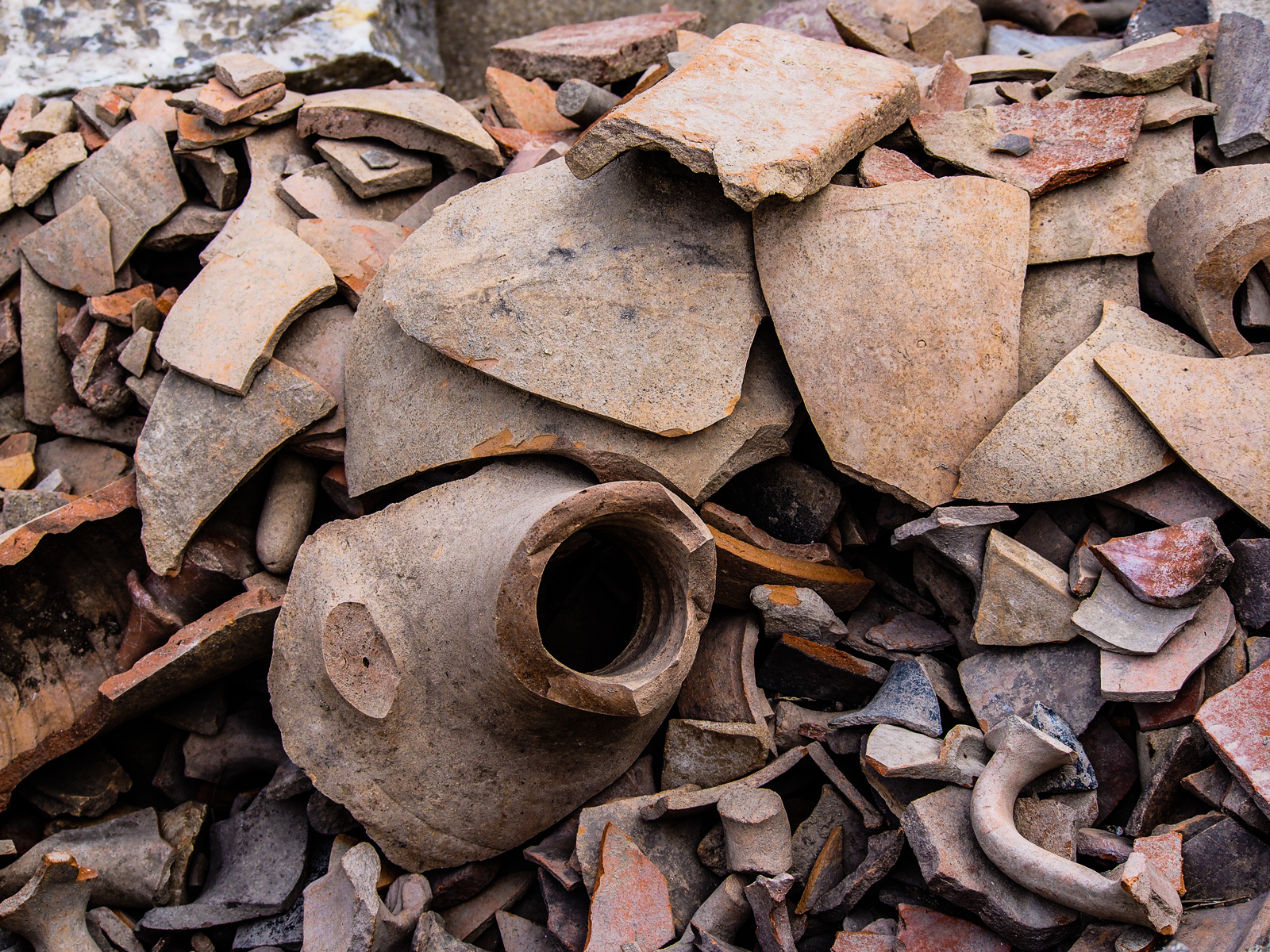 An image showing a large pile of broken pieces of pottery in different sizes and shapes. It is possible to see the upper half of a broken pot in the pile as well as several handles. The pieces are different colors, thicknesses, and shapes and it possible to assume that the pieces in the photo came from many different individual pots.