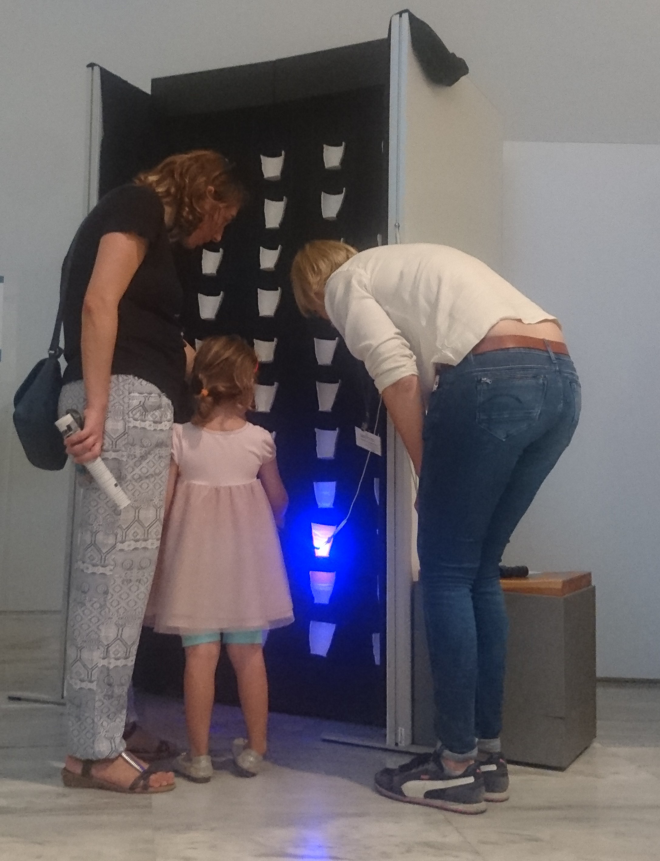 A mother and her daughter visiting the Tracing the Conical Cup exhibition are standing next to project team member Loes Opgenhaffen. They are facing an upright display of cups cut in half, and the young girl is using a ultraviolet flashlight to look at one of the cups on display.